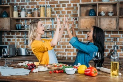 friends high five in the kitchen